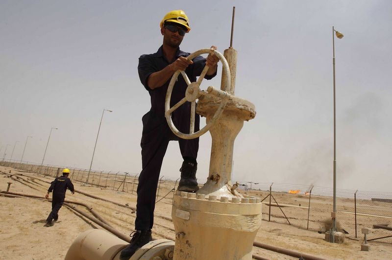 A worker adjusts the valve of an oil pipe as smoke rises from burning excess gas (in the background) in Zubair oilfield in Basra, 420 km (260 miles) southeast of Baghdad May 23, 2011. Italy's ENI is stepping up work in Iraq's Zubair oilfield despite aging facilities there and plans to drill about 68 new oil wells through next year to increase production, officials said. Picture taken May 23, 2011. REUTERS/Atef Hassan (IRAQ - Tags: ENERGY BUSINESS)