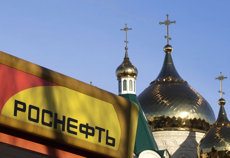 The logo of Russia's top crude producer Rosneft is seen on a gasoline station near a church in Stavropol, southern Russia, December 9, 2014. REUTERS/Eduard Korniyenko