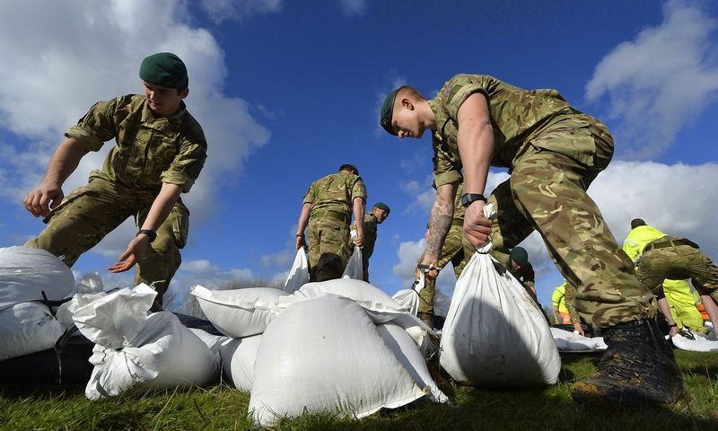 British army Royal Marines from 40 Commando lay sandbag water defences in the village of Moorland in south west England February 7, 2014. Many areas of the Somerset Levels have been underwater for over a month in the wettest January in Britain on record. Severe weather warnings for rain and gale force winds have been issued for the weekend. REUTERS/Toby Melville (BRITAIN - Tags: MILITARY ENVIRONMENT)