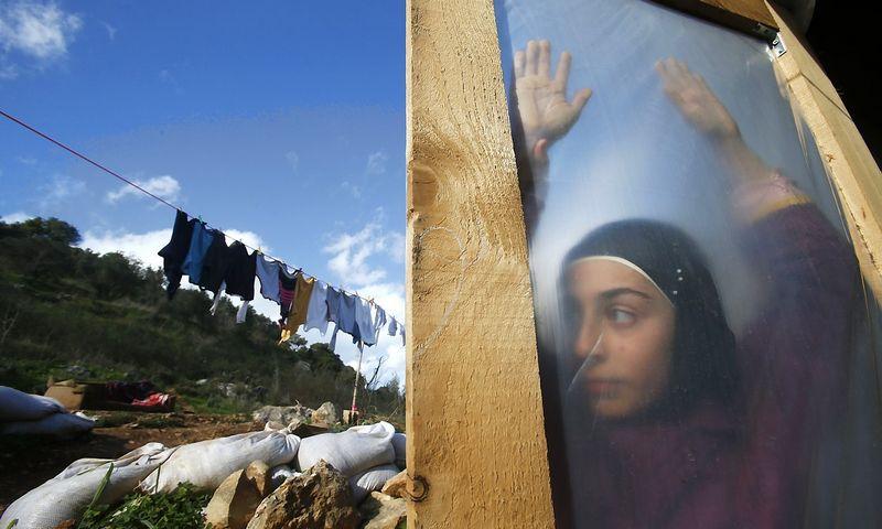 """Iš Sirijos nuo karo pabėgusi paauglė stovi vienoje Libano pabėgėlių stovyklų. (""""Reuters"""" / """"Scanpix"""") nuotr."""