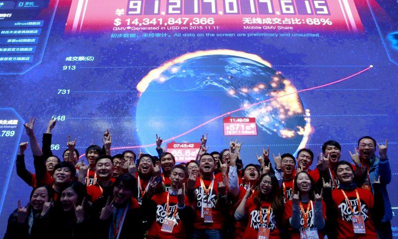 """""""Alibabos"""" darbuotojai pozuoja prie ekrano, rodančio Vienišių dienos prekybos rezultatus. Kimo Kyung-Hoono (""""Reuters"""" / """"Scanpix"""") nuotr."""