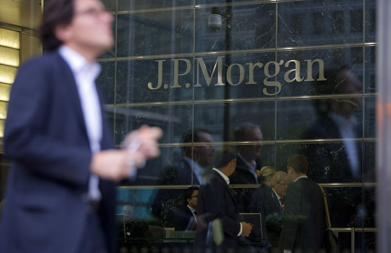 Workers are reflected in the windows of the Canary Wharf offices of JP Morgan in London in this file photo from September 19, 2013. JPMorgan Chase & Co, the largest U.S. bank, is reducing both its profit target and headcount in 2014, according to a Tuesday presentation.   REUTERS/Neil Hall/Files  (BRITAIN - Tags: BUSINESS)