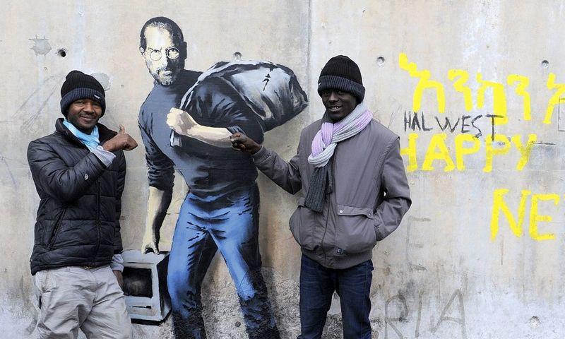 """Banksy darbas ant sienos šalia pabėgėlių stovyklos Kalė mieste, Prancūzijoje. Sarah'os Alcalay (""""Sipa""""/""""Scanpix"""") nuotr."""