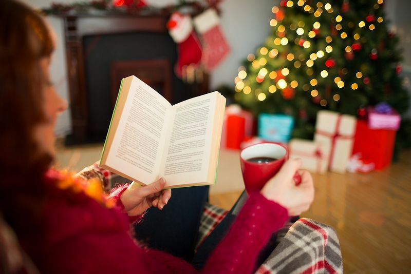 Red hair reading and drinking coffee at christmas at home in the living room