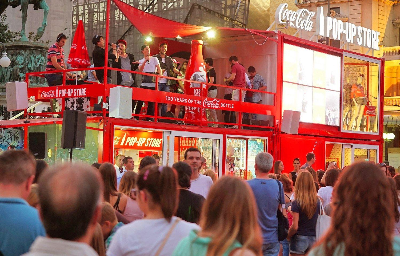 """Pirmą kartą į Lietuvą kelioms savaitėms atkeliauja tradicinis kilnojamas """"Coca-Cola"""" paviljonas."""