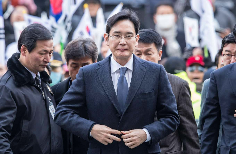 """Ponas Lee žengia į teismo salę pareigūnų apsuptyje. Lee Jae-yong (""""Scanpix""""/""""Reuters"""") muotr."""