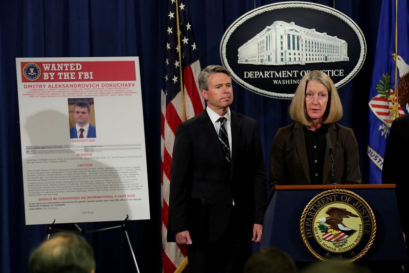 """Plakate kairėje – vienas iš kaltinamųjų. Yuri Gripas (""""Scanpix""""/""""Reuters"""") muotr."""