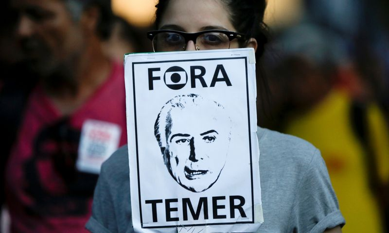 """Protestuojanti moteris rankose laiko Michelio Temerio, Brazilijos prezidento, atvaizdą. Bruno Kelly (""""Reuters"""" / """"Scanpix"""") nuotr."""
