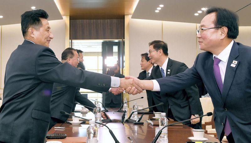 """Kairėje – Jon Jong Su, Šiaurės Korėjos delegacijos vadovas, dešinėje – Chun Hae-sungas, Pietų Korėjos susivienijimo ministras. """"Reuters"""" nuotr."""