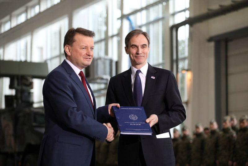 """Lenkijos gynybos ministras Mariuszas Blaszczakas ir JAV ambasadorius Lenkijoje Paulas W. Jonesas pasirašo susitarimą dėl raketų. Slawomiro Kaminskio (""""Agencja Gazeta"""" / """"Scanpix"""") nuotr."""