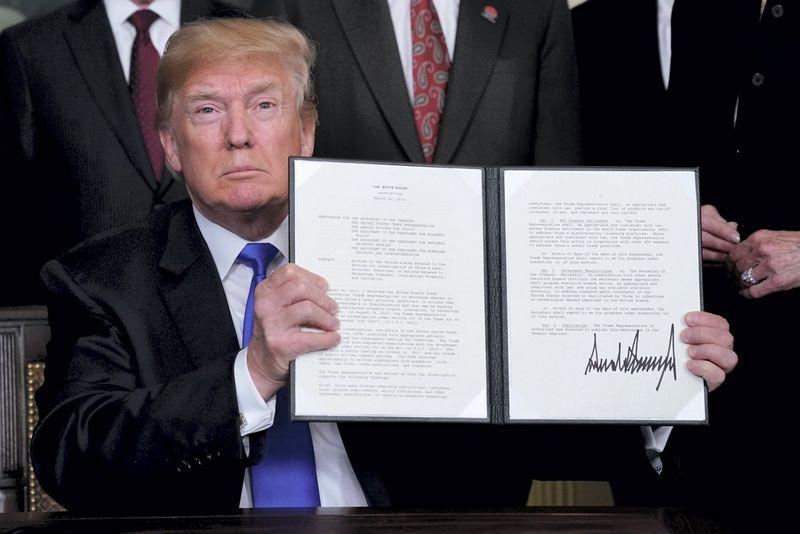 """Donaldas Trumpas rodo memorandumą dėl muitų Kinijos prekėms. Jonathano Ernsto (""""Reuters"""" / """"Scanpix"""") nuotr."""