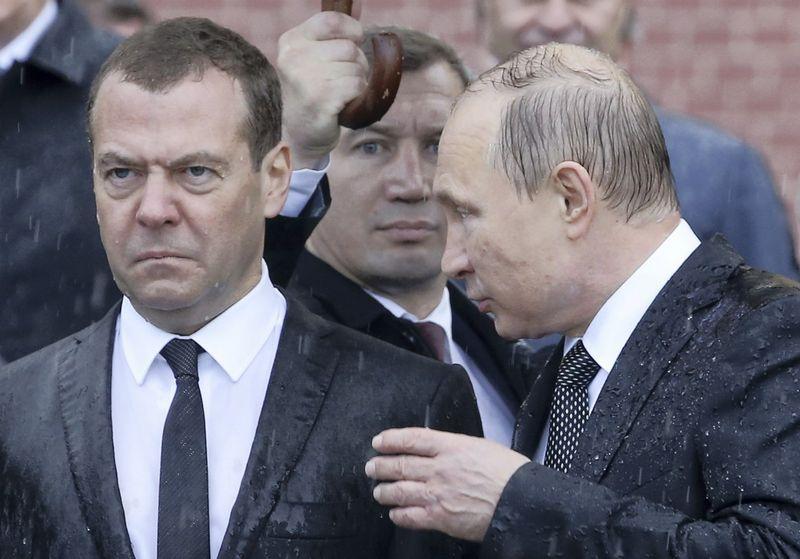"""Vis garsiau kalbama, kad Rusijos prezidentas Vladimiras Putinas (dešinėje) ruošiasi atsisveikinti su premjeru Dmitrijumi Medvedevu. Sergejaus Karpuchino (""""Reuters"""") nuotr."""