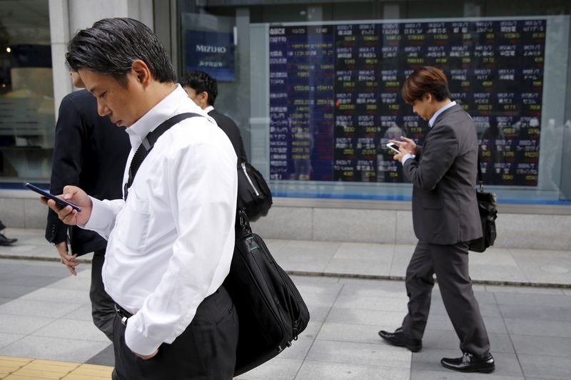 Businessmen look at their mobile phones in front of an electronic stock quotation board outside a brokerage in Tokyo, Japan, October 23, 2015. Asia extended a global stocks rally on Friday after the European Central Bank signaled its readiness to inject more stimulus, helping the dollar scale a fresh two-month peak against the euro. REUTERS/Toru Hanai
