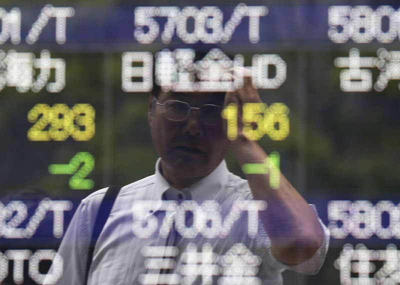 A man wipes his head as he is reflected on a stock quotation board outside a brokerage in Tokyo June 10, 2014. Asia stocks nudged three-year highs on Tuesday on rising optimism over global growth prospects and a record-run on Wall Street, helping lift Treasury yields and the dollar. REUTERS/Issei Kato (JAPAN - Tags: BUSINESS)