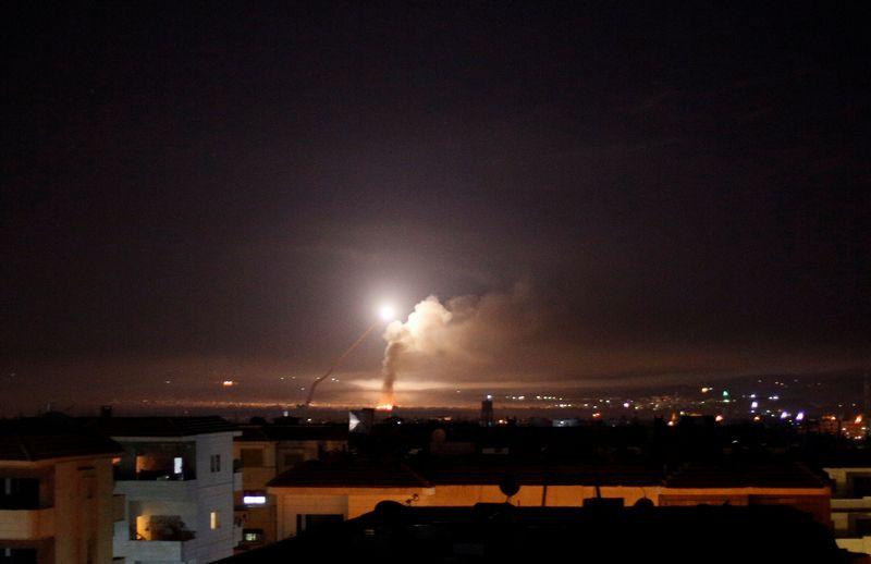 """Nuo raketos smūgio kylantys dūmai matomi iš Sirijos Damasko miesto. Omaro Sanadiki (""""Reuters"""" / """"Scanpix"""") nuotr."""