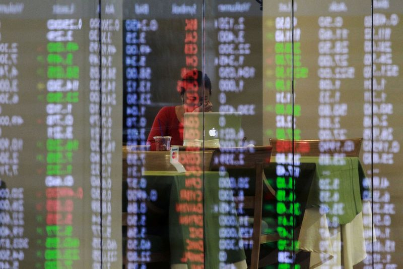 Philippine Stocks Exchange (PSE) share prices are reflected on a glass panel as broker takes a break in Manila's Makati financial district February 6, 2014. Major Southeast Asian stock markets rose on Thursday, with Singapore rebounding from a 14-month closing low hit in the previous session amid gains in Asian stock markets, while bargain hunting helped Thai shares plagued with political risks.  REUTERS/Romeo Ranoco  (PHILIPPINES - Tags: BUSINESS TPX IMAGES OF THE DAY)