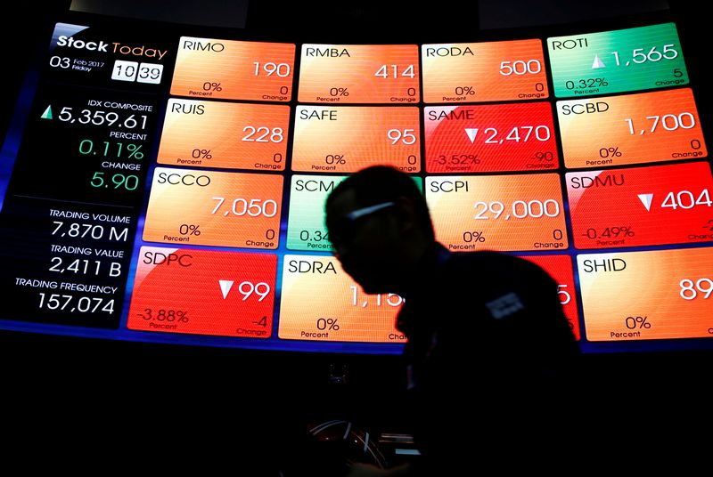 FILE PHOTO - A worker walks next to an electronic stock board at the Indonesia Stock Exchange in Jakarta, Indonesia February 3, 2017. REUTERS/Beawiharta/File Photo