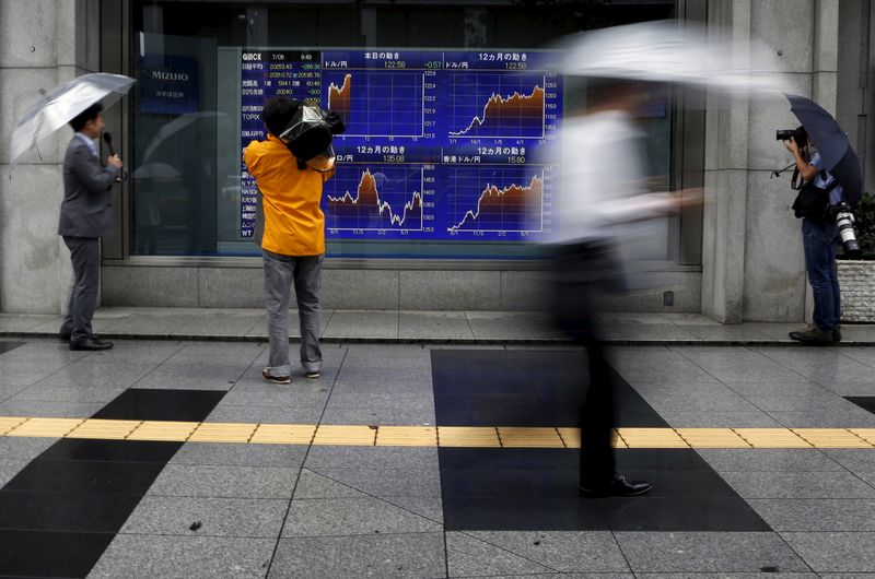 Videographer films an electronic board showing the graphs of exchange rates between the Japanese yen, the U.S. dollar and Euro outside a brokerage in Tokyo, Japan, July 6, 2015. The euro and stock prices fell sharply in Asia on Monday after the Greeks had overwhelmingly rejected austerity measures demanded in return for bailout money, putting in doubt its continued place in the single currency. U.S. equity futures dropped around 1.4 percent while Japan's Nikkei shares fell 1.4 percent and MSCI's broadest index of Asia-Pacific shares outside Japan dropped 0.5 percent. REUTERS/Yuya Shino