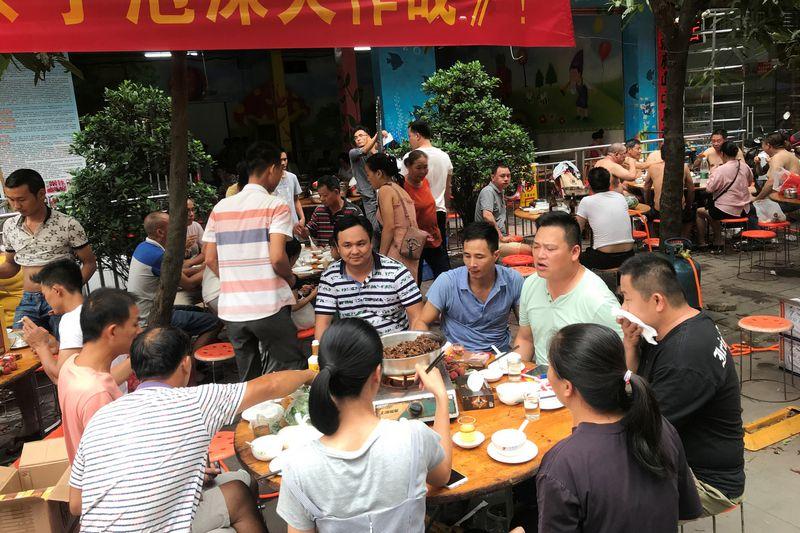 """Prie stalų su šuniena susėdę kinai Julino gatvėse. """"Reuters""""/""""Scanpix"""" nuotr."""