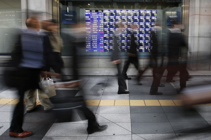 Passers-by walk past a stock quotation board outside a brokerage in Tokyo December 4, 2013. Most Asian shares slumped on Wednesday as the prospects of a reduction in the U.S. Federal Reserve's stimulus early next year prompted investors to cash in gains from recent rallies. MSCI's broadest index of Asia-Pacific shares outside Japan fell 0.4 percent after earlier hitting its lowest levels in almost two weeks, while Japan's Nikkei share average dropped 2.2 percent from a six-year closing high set on Tuesday. REUTERS/Toru Hanai (JAPAN - Tags: BUSINESS)