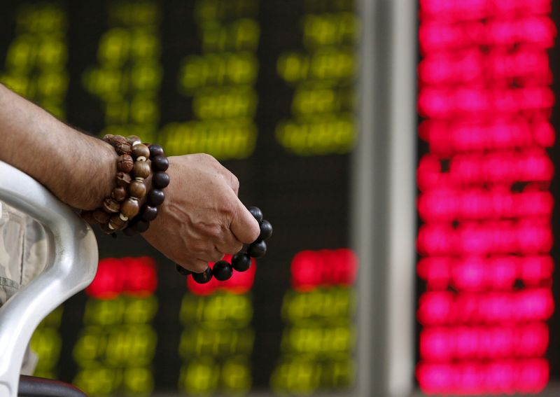 FILE PHOTO: An investor holds onto prayer beads as he watches a board showing stock prices at a brokerage office in Beijing, China, July 6, 2015.  REUTERS/Kim Kyung-Hoon/File Photo