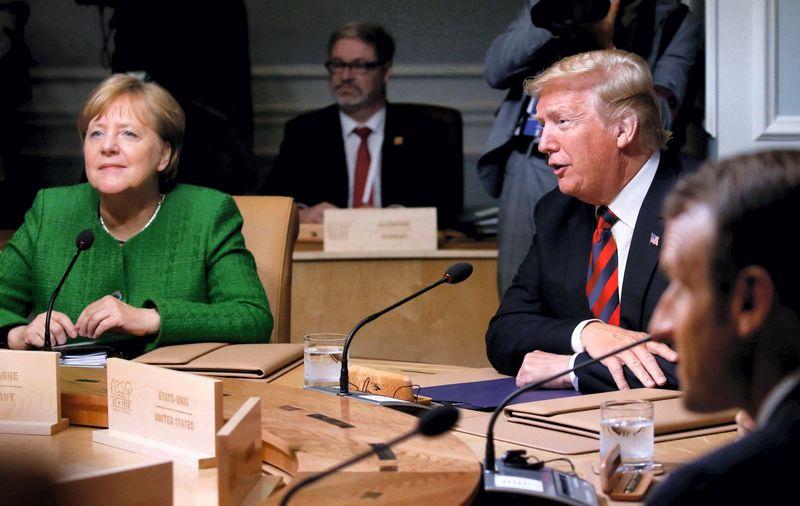 """Donaldas Trumas, JAV vadovas, ir Angela Merkel, Vokietijos kanclerė, per G7 susitikimą Kanadoje. Leah Millis (""""Reuters"""" / """"Scanpix"""") nuotr."""