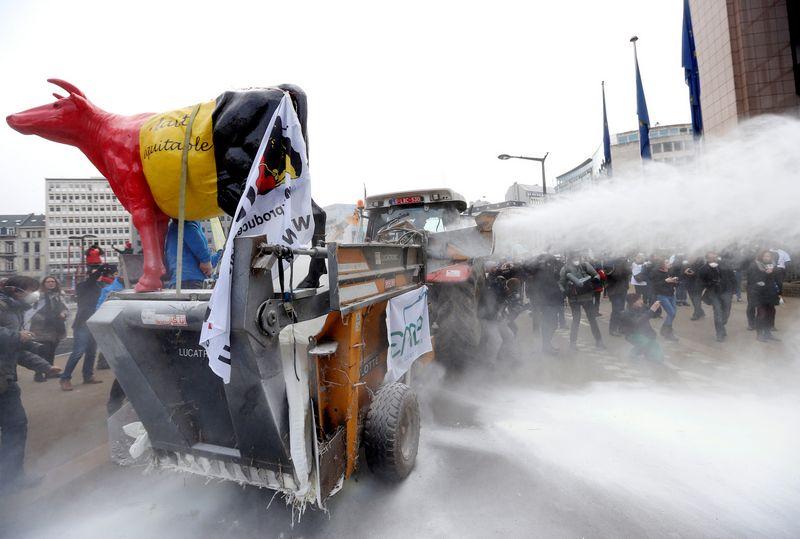 """Praėjusiais metais protestuodami ūkininkai Briuselyje išbarstė šimtus kilogramų pieno miltelių. Francois Lenoiro (""""Reuters"""" / """"Scanpix"""") nuotr."""