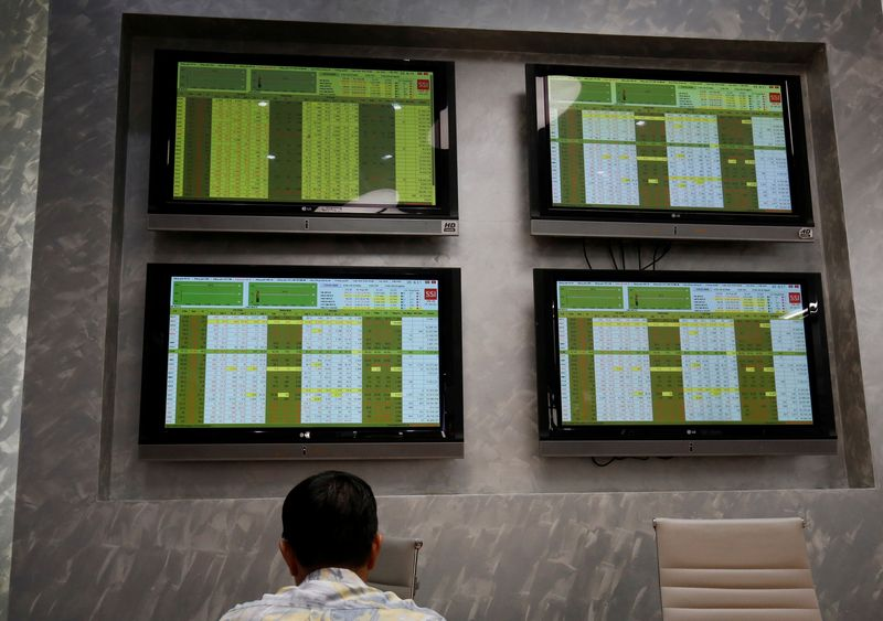An investor sits in front of screens showing stock board information at a securities company in Hanoi, Vietnam July 6, 2018. Picture taken July 6, 2018. REUTERS/Kham