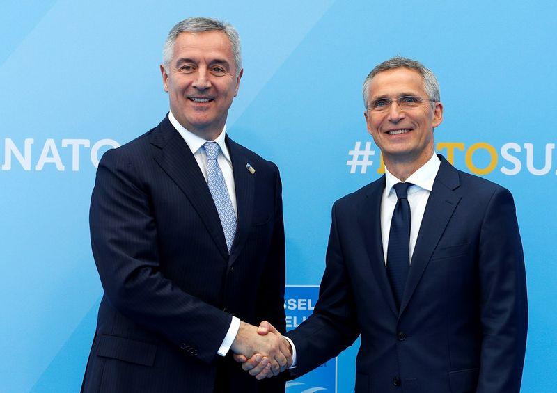 Juodkalnija kol kas yra paskutinė prie NATO prisijungusi valstybė. Šalies prezidentas Miko Džukanovičius sveikinasi su NATO generaliniu sekretoriumi Jensu Stoltenbergu. Paulos Hannos (Reuters / Scanpix) nuotr.