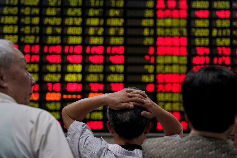 FILE PHOTO: Investors look at an electronic board showing stock information at a brokerage house in Shanghai, China June 20, 2018. REUTERS/Aly Song/File Photo