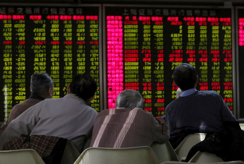 FILE PHOTO: Men look at an electronic board showing stock information at a brokerage house in Beijing, China, January 5, 2016. REUTERS/Kim Kyung-Hoon/File Photo