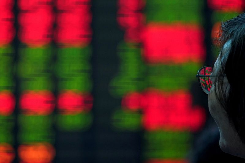 FILE PHOTO An investor looks at an electronic board showing stock information at a brokerage house in Shanghai, China July 6, 2018. REUTERS/Aly Song/File Photo GLOBAL BUSINESS WEEK AHEAD