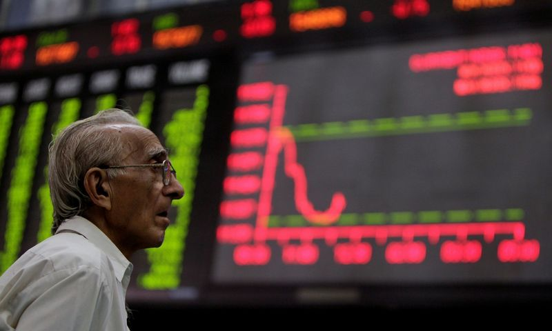 FILE PHOTO: A man monitors an electronic board displaying stock prices at the Karachi Stock Exchange August 5, 2011. Pakistani stocks provisionally ended 3.78 percent lower on Friday as foreign investors offloaded their holdings amid a global sell-off, while local investors remained cautious, dealers said. REUTERS/Akhtar Soomro/File Photo