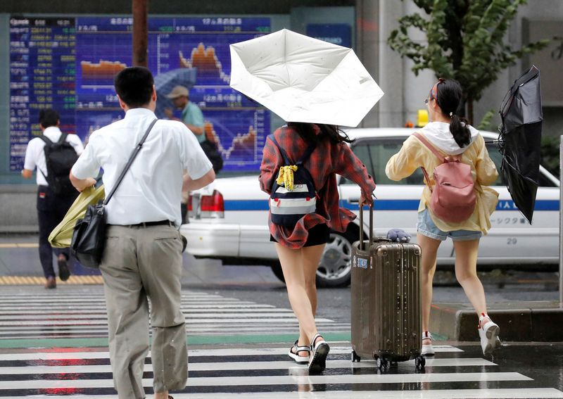 Passersby using umbrellas struggle against a heavy rain and wind in front of an electronic stock quotation board as Typhoon Shanshan approaches Japan's mainland in Tokyo, Japan August 8, 2018.   REUTERS/Toru Hanai