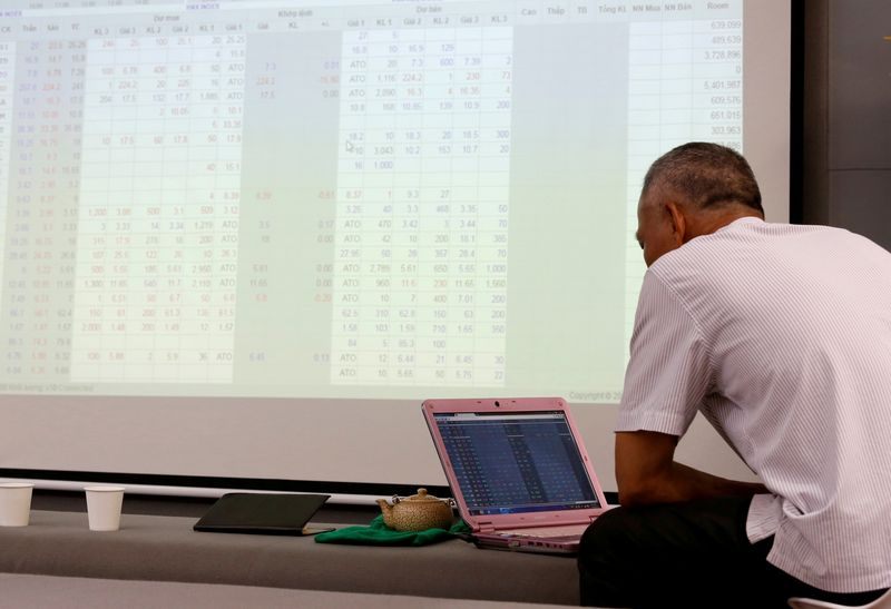 FILE PHOTO: An investor looks at a screen showing stock board information at a securities company in Hanoi, Vietnam July 6, 2018. Picture taken July 6, 2018. REUTERS/Kham/File Photo