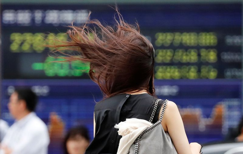 A woman struggles against strong wind caused by Typhoon Jebi, in front of an electronic stock quotation board in Tokyo, Japan, September 4, 2018.   REUTERS/Toru Hanai