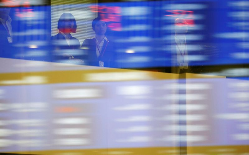 Visitors are seen as market prices are reflected in a glass window at the Tokyo Stock Exchange (TSE) in Tokyo, Japan, October 1, 2018.   REUTERS/Toru Hanai