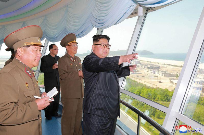 """Šiaurės Korėjos lyderis Kim Jong Unas apžiūri Vonsano Kalmos turistų zonoje stotomą kurotą, kuris, tikimasi, kasmet sutrauks milijonus poilsiautojų iš užsienio. """"Reuters"""" / """"Scanpix"""" nuotr."""