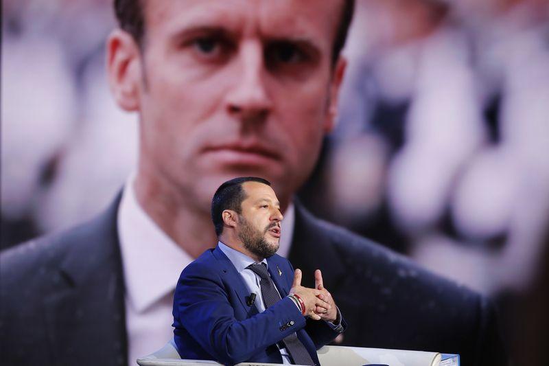"Italijos vicepremjeras Matteo Salvini ir Prancūzijos prezidentas Emmanuelis Macronas (fone). ""La Presse"" / ""Scanpix"" nuotr."