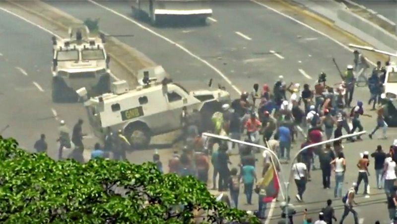 Neramumai Venesueloje. Kariuomenės šarvuotis Karakase antradienį rėžėsi į žmones (REUTERS/SCANPIX nuotr.)