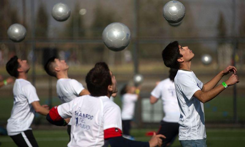 """2019 m. birželio 16 d. šimtai žmonių Santjage vienu metu galvomis mušinėjo kamuolius, norėdami patekti į Guinnesso rekordų knygą. Claudio Reyeso (AFP/""""Scanpix"""") nuotr."""
