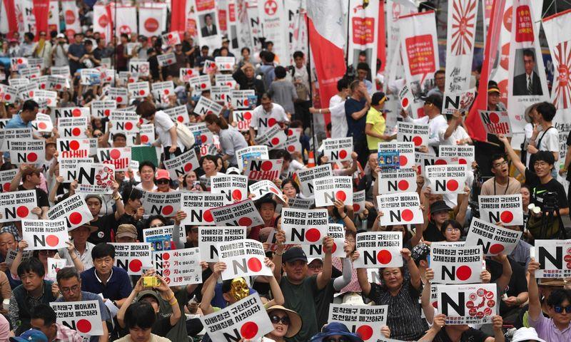 """Prie Japonijos ambasados Seule protestuojantys pietų korėjiečiai laiko plakatus """"Ne (Japonijai)"""". Jung Yeon Je (AFP / """"Scanpix"""") nuotr."""