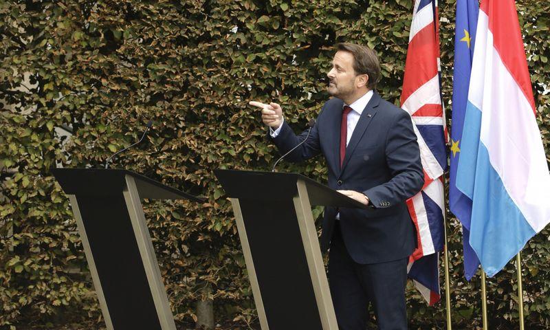 """Liuksemburgo premjeras Xavieras Bettelis spaudos konferencijoje šalia tuščios tribūnos, kuri buvo skirta Borisui Johnsonui. Olivier Matthys (AP/""""Scanpix"""") nuotr."""
