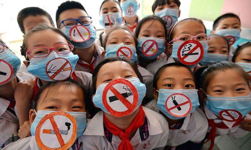 """Vienose Kinijos mokyklose vaikai ruošia projektus, minėdami Pasaulinę dieną be tabako, kitose ant sienų puikuojasi tabako bendrovių šūkiai. """"AFP Photo"""" / """"Scanpix"""" nuotr."""