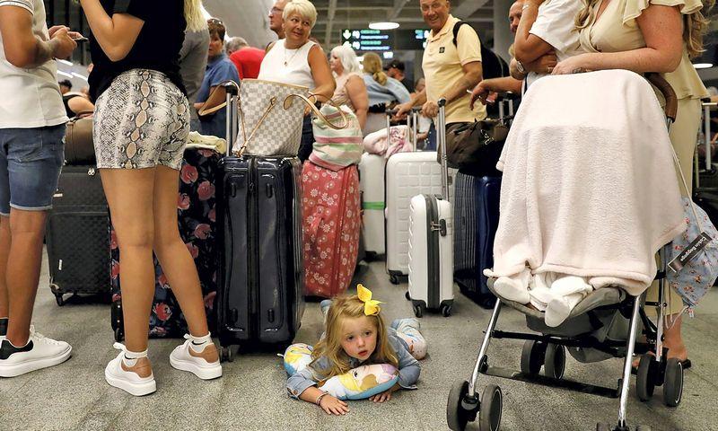 """Britų turistai laukia eilėje Dalamano oro uoste Turkijoje. Umito Bekto (""""Reuters"""" / """"Scanpix"""") nuotr."""
