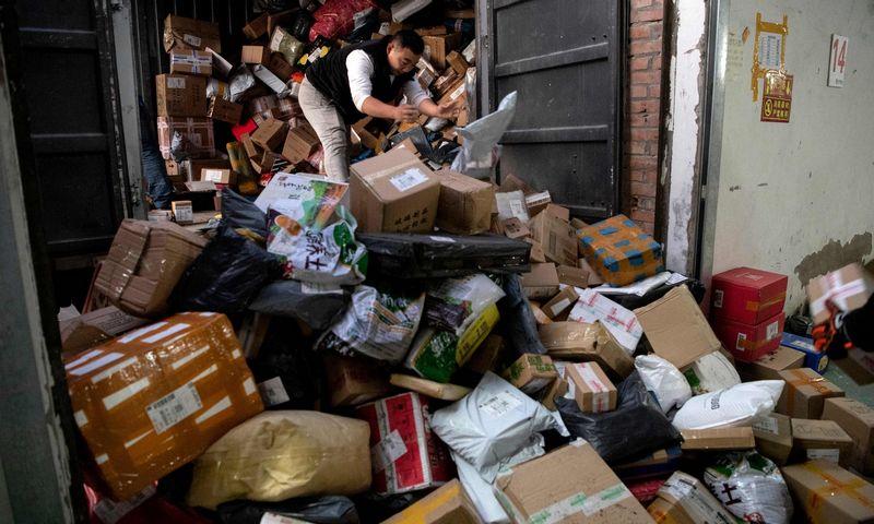"""Pristatymo tarnybos darbuotojas Pekine rūšiuoja siųsti paruoštas Vienišių dienos prekes. AFP / """"Scanpix"""" nuotr."""