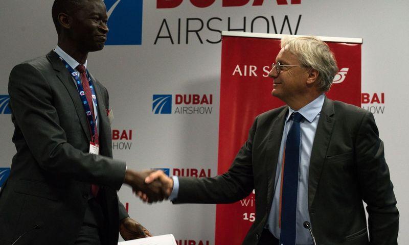 """""""Air Senegal"""" vadovas Ibrahimas Kane (iš kairės) spaudžia ranką """"Airbus"""" komercijos vadovui Christianui Schererui Dubajuje vykstančioje aviacijos parodoje. Jon Gambrell (AP / """"Scanpix"""") nuotr."""