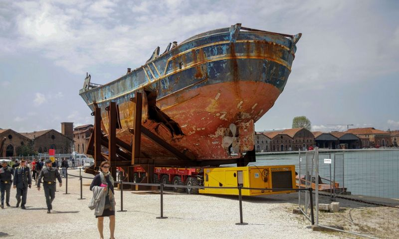 Ar etiška eksponuoti laivą, kuriame žuvo tiek žmonių, net jei tai iš tiesų priartina tragediją, o netoliese stovinčios už šį laivą didesnės privačios jachtos dar išryškina neteisybę? Ant ko pykti? Mirco Toniolo / AGF / SIPA nuotr.