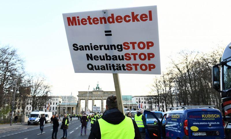 """2019 m. gruodžio 9 d. ant demonstracijoje prieš kainų užšaldymą protestavusio staybininko palakato užrašyta: """"Nuomos kontrolė = STOP renovcijai, STOP naujai statybai, STOP kokybei."""" Annegret Hilse (""""Reuters"""" / Scanpix"""") nuotr."""