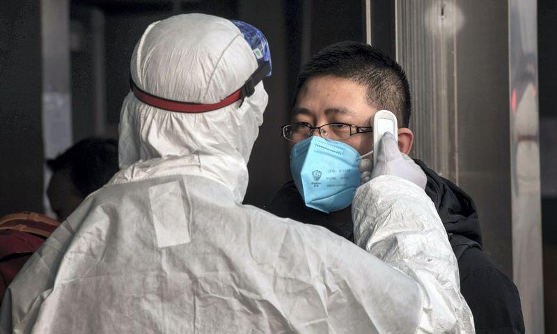 Apsaugos darbuotojas matuoja keleivio temperatūrą Pekino metro stotyje.  Nicolas Asfouri (AFP/Scanpix) nuotr.